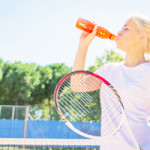 A tennis player drinks a sports drink